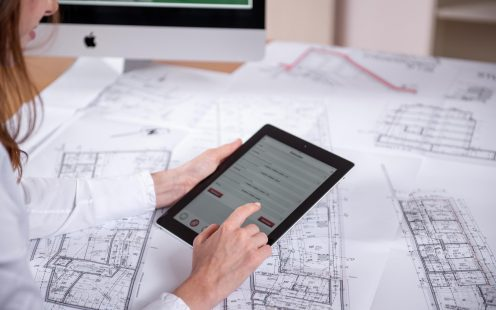 Woman at workplace with blueprint holding tablet computer